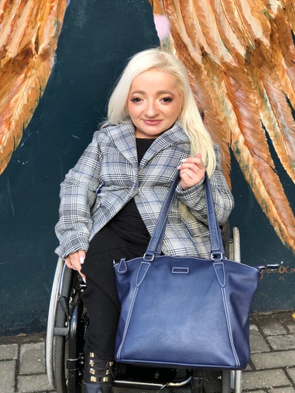Sam Renke holding her accessible wheelchair handbag in navy