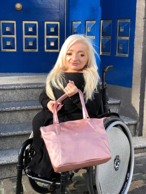 Sam Renke holding her rose gold handbag