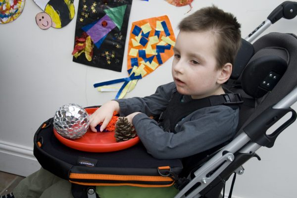 Trabasack Curve Connect wheelchair lap tray and bag on a disabled child's lap with a toy on top