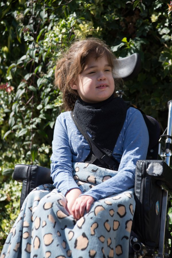 Disabled girl wearing Seenin fleece wheelchair leg cover in blue leopard print