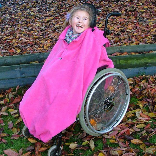 Disabled girl in woodland in fuchsia Seenin total fleece wheelchair cover
