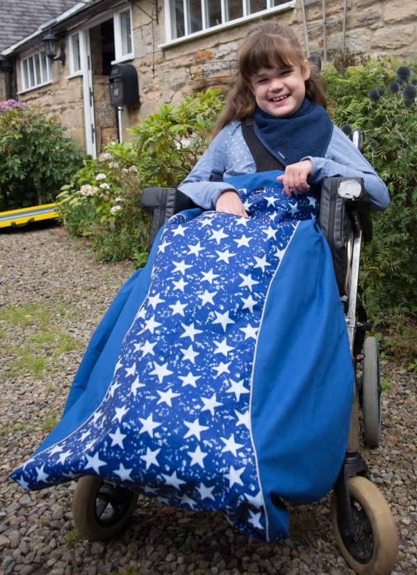 Disabled girl in navy star print Seenin waterproof wheelchair leg cover