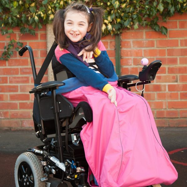 Image is a photograph of a young girl with brown hair in bunches, sat smiling in a wheelchair with a pink waterproof leg cover