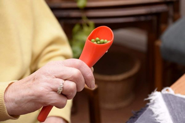 Image is a photograph of an older lady wearing a yellow jumper, holding a S'Up Spoon Mini filled with garden peas