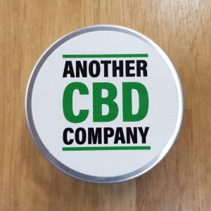 """Image is a photograph of a metal lidded balm tin on a wooden table, with text that reads: """"Another CBD Company"""""""