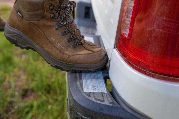 Image is a photograph of a boot standing on a strip of Cat Tongue Grip Tape that has been attached to the back footplate of a vehicle