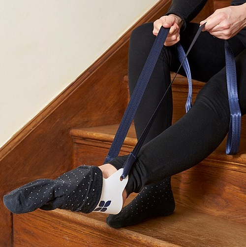Navy sock dressing aid being used to put on a white sock by a woman sat on the stairs